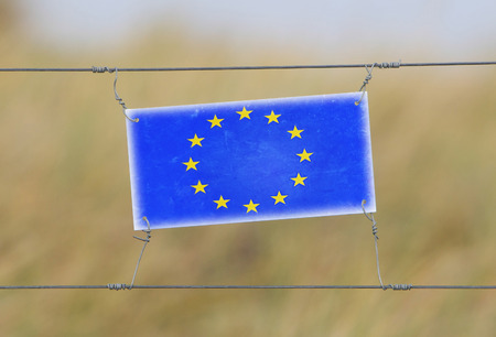 Border fence - Old plastic sign with a flag - European Union photo