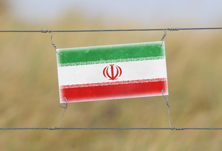 Border fence - Old plastic sign with a flag - Iran photo