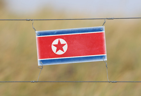 Border fence - Old plastic sign with a flag - North Korea photo