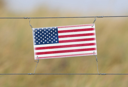 Border fence - Old plastic sign with a flag - USA photo