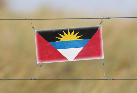 Border fence - Old plastic sign with a flag - Antigua and Barbuda photo