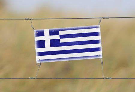 Border fence - Old plastic sign with a flag - Greece photo
