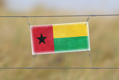 Border fence - Old plastic sign with a flag - Guinea Bissau photo