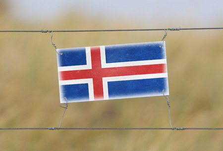 Border fence - Old plastic sign with a flag - Iceland photo