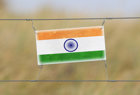 Border fence - Old plastic sign with a flag - India photo