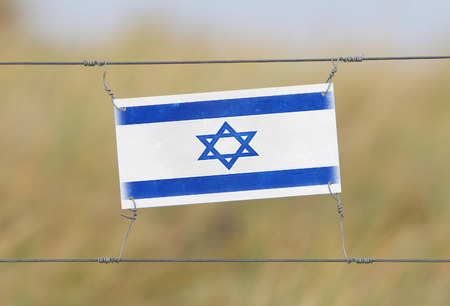 Border fence - Old plastic sign with a flag - Israel photo
