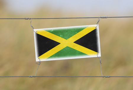 Border fence - Old plastic sign with a flag - Jamaica photo