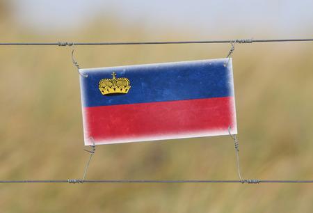 Border fence - Old plastic sign with a flag - Liechtenstein photo