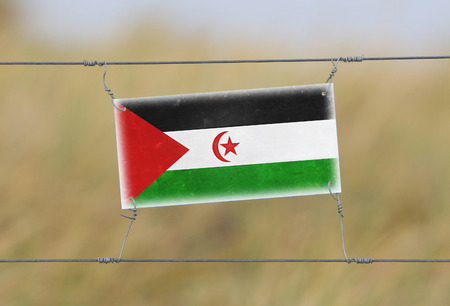 Border fence - Old plastic sign with a flag - Western Sahara photo