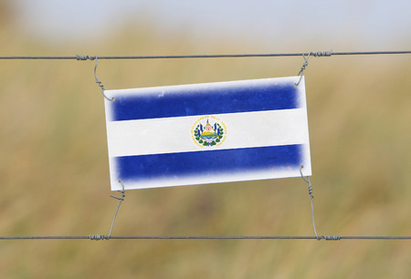 Border fence - Old plastic sign with a flag - El Salvador photo