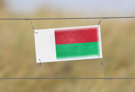 Border fence - Old plastic sign with a flag - Madagascar photo