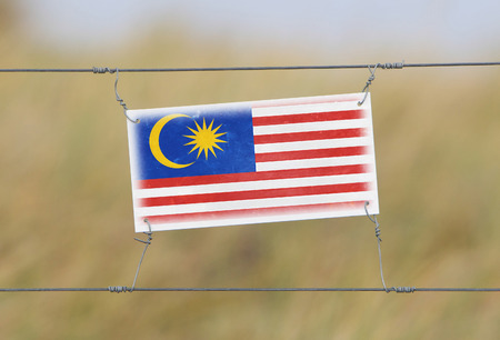 Border fence - Old plastic sign with a flag - Malaysia photo