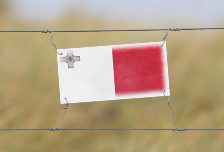 Border fence - Old plastic sign with a flag - Malta photo
