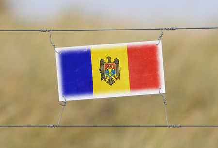 Border fence - Old plastic sign with a flag - Moldova photo
