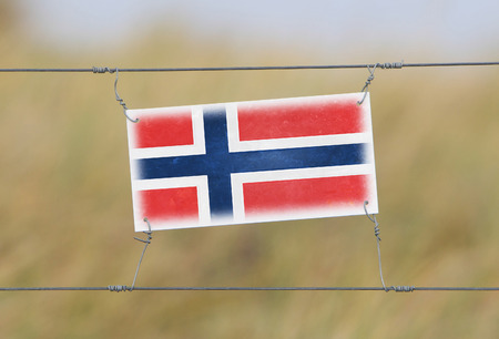 Border fence - Old plastic sign with a flag - Norway photo