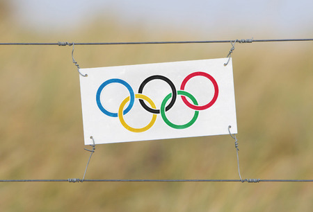 olympic symbol: Border fence - Old plastic sign with a flag - Olympic rings