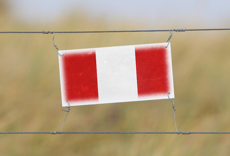 Border fence - Old plastic sign with a flag - Peru photo