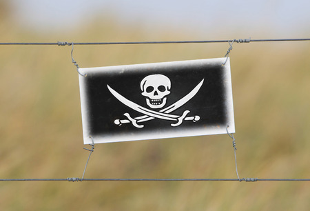 Border fence - Old plastic sign with a flag - Pirate photo