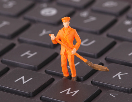Miniature worker is cleaning a computer keyboard photo