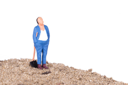 Miniature worker with a shovel on a mountain of sand photo