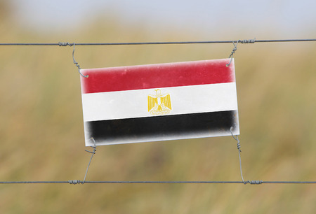 Border fence - Old plastic sign with a flag - Egypt photo
