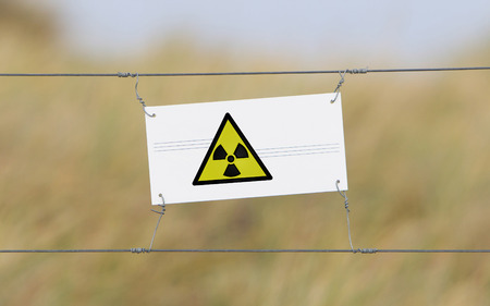 Border fence - Old plastic sign with a flag - Radiation photo