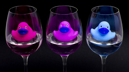 Pink, purple and blue rubber ducks in wineglasses, dark background photo