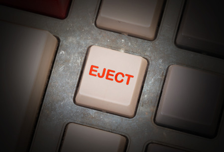 triggers: White button on a dirty old panel, selective focus - eject Stock Photo