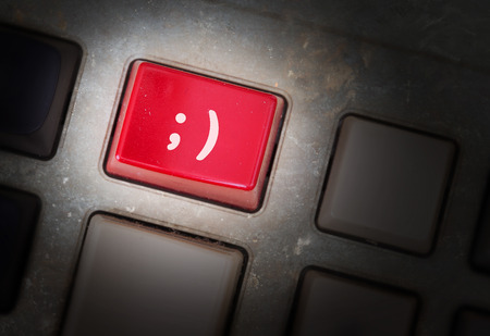 triggers: Red button on a dirty old panel, selective focus - smiley Stock Photo