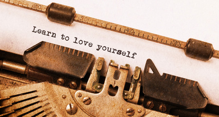 Vintage typewriter, old rusty, warm yellow filter, learn to love yourself photo