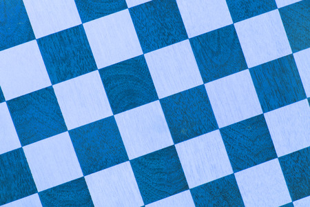 Very old wooden chess board, isolated close-up, blue