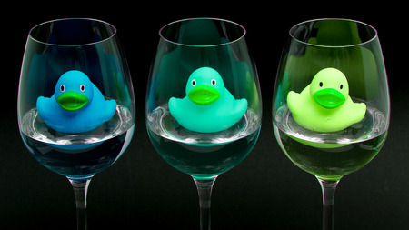 Blue and green rubber ducks in wineglasses, dark background photo