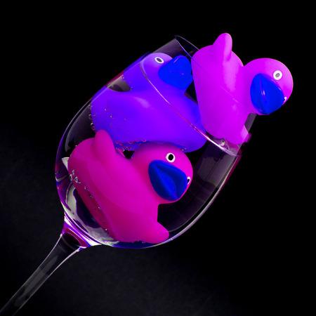 thirsty bird: Pink and purple rubber ducks in wineglasses, dark background