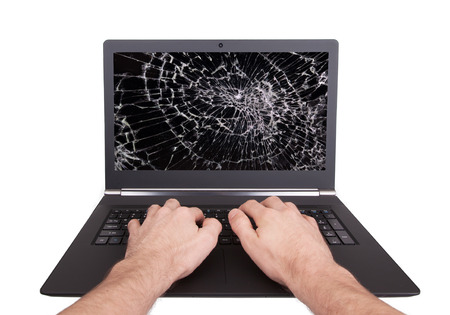 Man working on a laptop with a broken screen, black photo