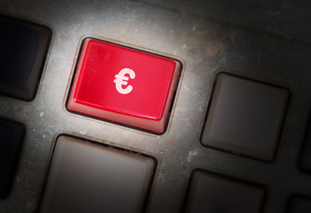 triggers: Red button on a dirty old panel, selective focus - euro sign
