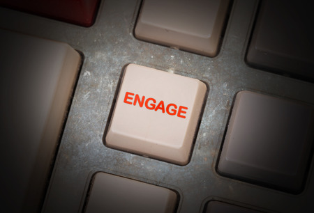triggers: White button on a dirty old panel, selective focus - engage Stock Photo
