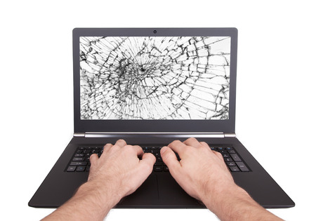 Man working on a laptop with a broken screen, white photo