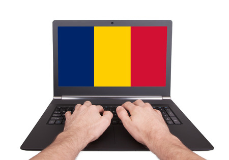 Hands working on laptop showing on the screen the flag of Romania photo