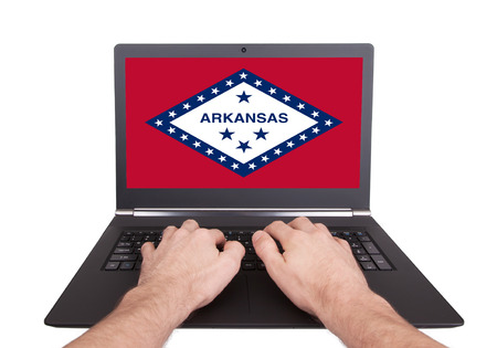 Hands working on laptop showing on the screen the flag of Arkansas photo