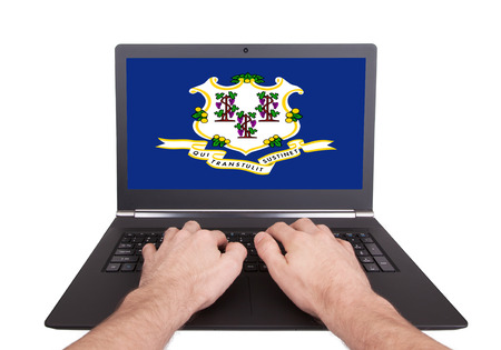 Hands working on laptop showing on the screen the flag of Connecticut photo