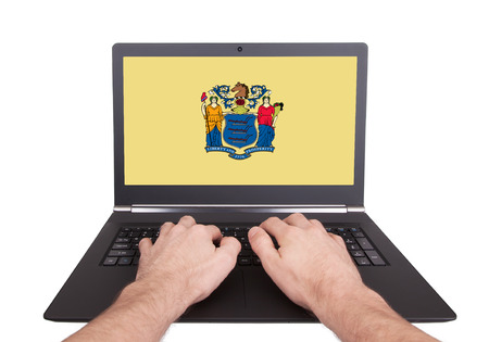 Hands working on laptop showing on the screen the flag of New Jersey photo