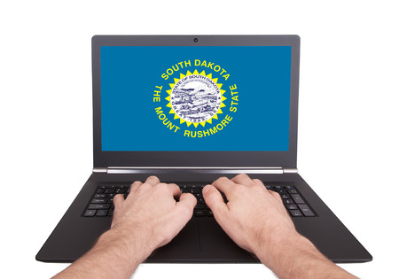 Hands working on laptop showing on the screen the flag of South Dakota photo