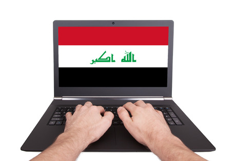 Hands working on laptop showing on the screen the flag of Iraq photo