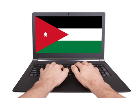 Hands working on laptop showing on the screen the flag of Jordan photo