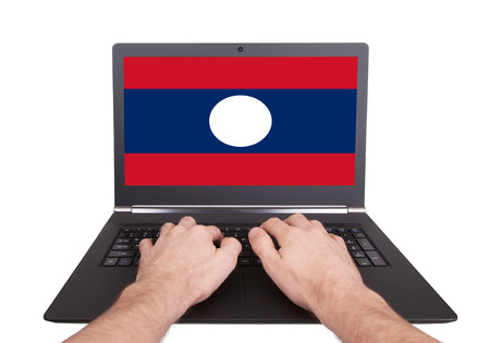 Hands working on laptop showing on the screen the flag of Laos photo