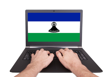Hands working on laptop showing on the screen the flag of Lesotho photo