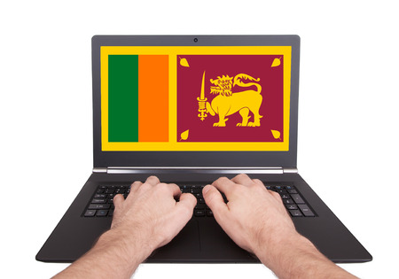 Hands working on laptop showing on the screen the flag of Sri Lanka photo