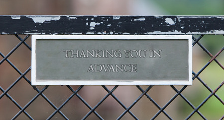 thanking: Sign hanging on an old metallic gate - Thanking you in advance Stock Photo
