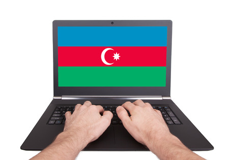 Hands working on laptop showing on the screen the flag of Azerbaijan photo