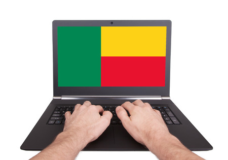 Hands working on laptop showing on the screen the flag of Benin photo